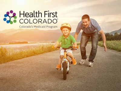 Health First Colorado - boy father bike with logo